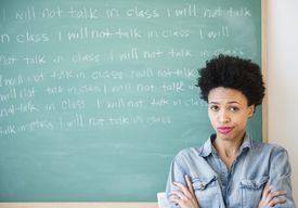 Black woman writing lines on chalkboard for disciplinary probation