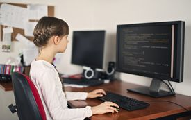 Little girl learning to code on desktop computer at home