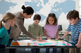 Teacher and kids looking at a map on a light table
