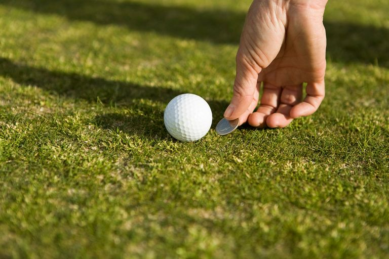 Person marking a golf ball position on the green