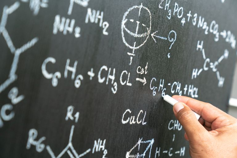 Senior chemistry professor writing on the board