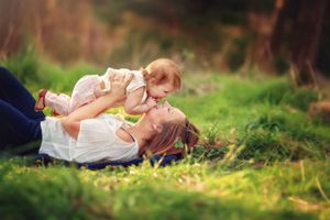 Woman With Child Lying in Grass