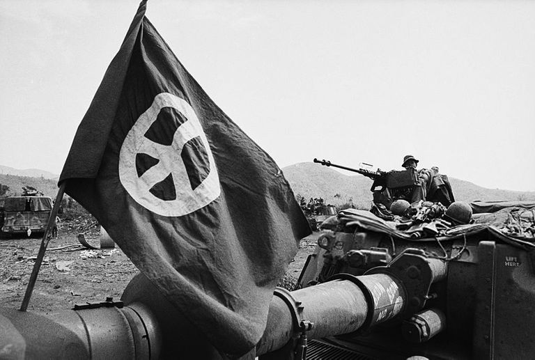 Flag with peace sign flying over an armored vehicle and soldiers.
