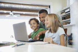 homework - father and children using computer for homework