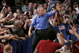 George W. Bush on the campaign trail waving at a gathered crowd.