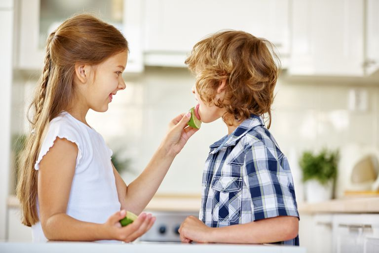 Children tasting limes in a kitchen