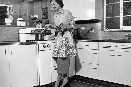 Woman stirring pot at stove, circa 1950s.