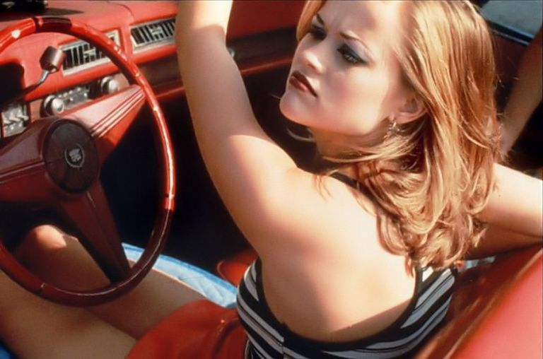Reese Witherspoon sitting behind wheel of red car
