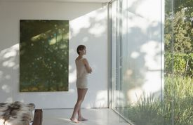 A woman facing a large window