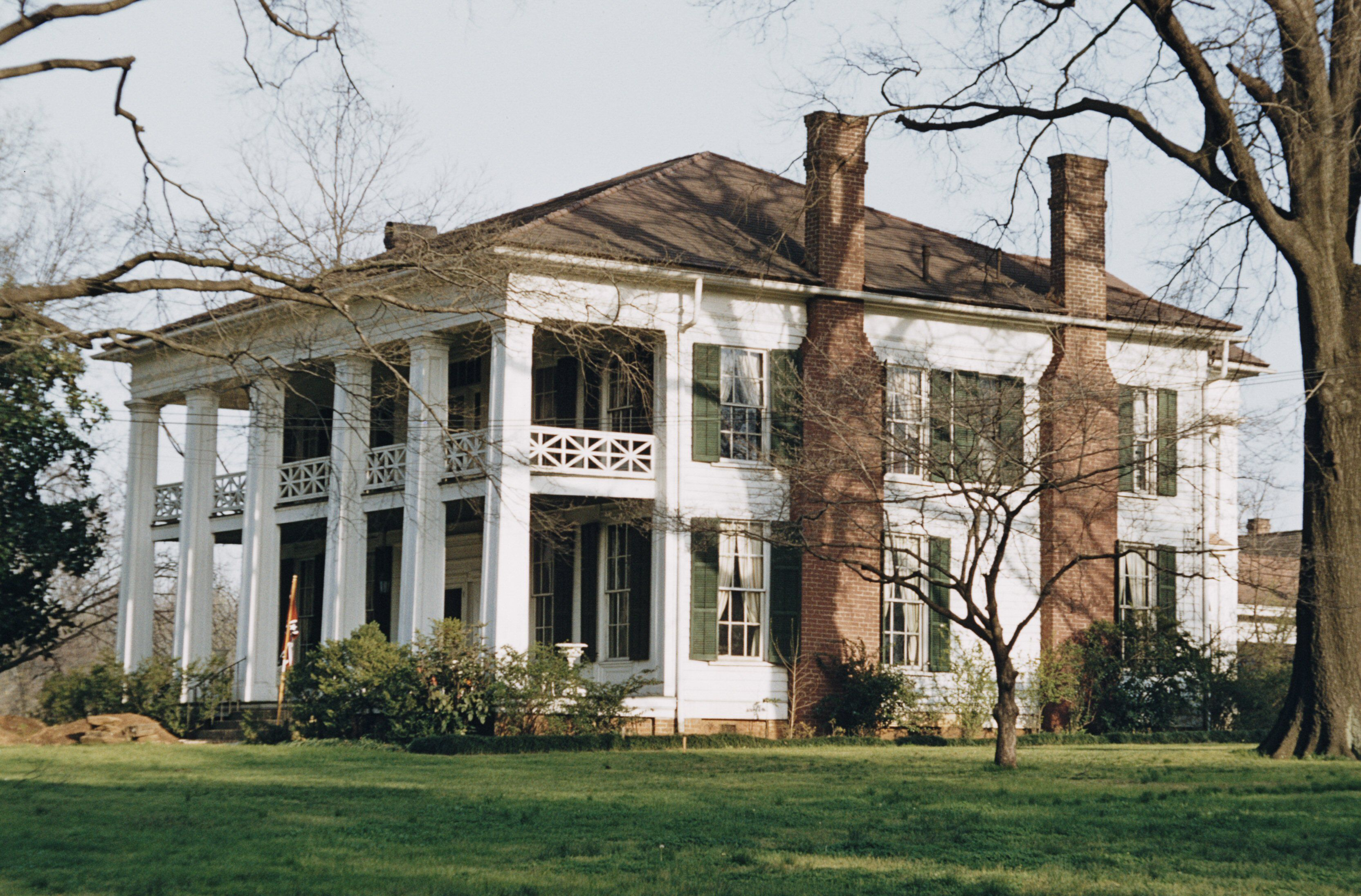 Large, 2 story white plantation home, with two chimneys and Roman lattice on the second story balcony