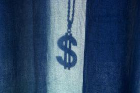 The shadow of a dollar medallion behind blue curtains.