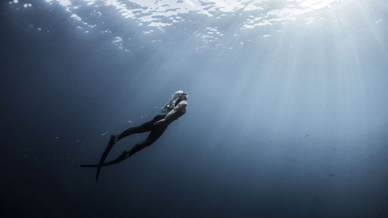 Underwater view of female free diver moving up towards sun rays, New Providence, Bahamas
