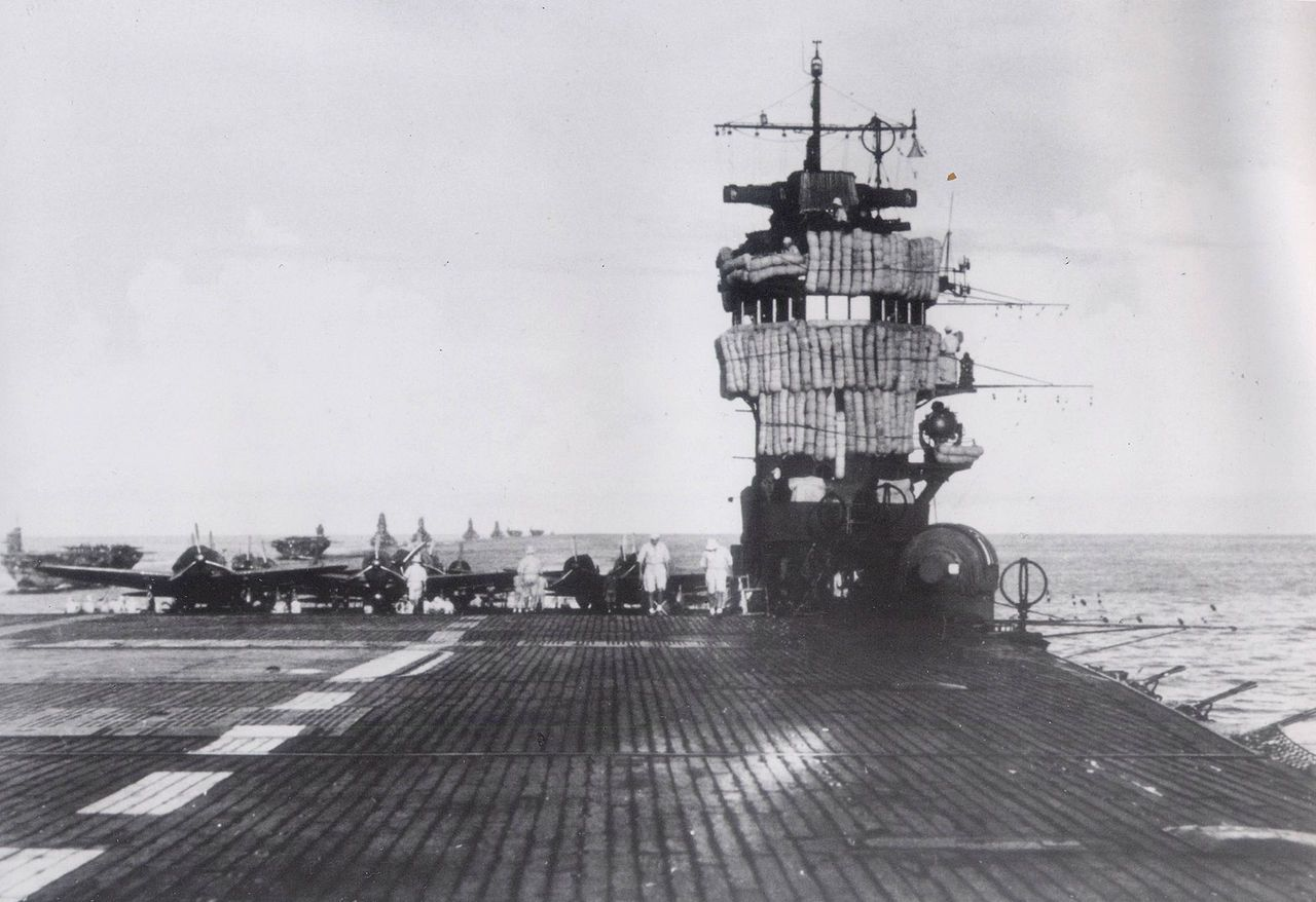 Flight deck of carrier Akagi with island on the right and aircraft parked on deck.