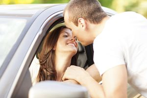 Young couple getting ready to kiss, with car