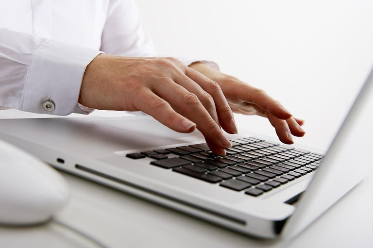 Close-up hands typing on computer keyboard.