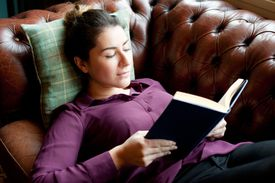 Woman lying on sofa reading book.