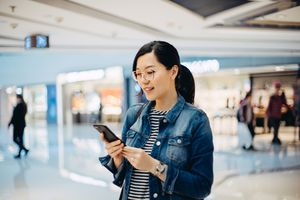 Young woman using smartphone in shopping mall