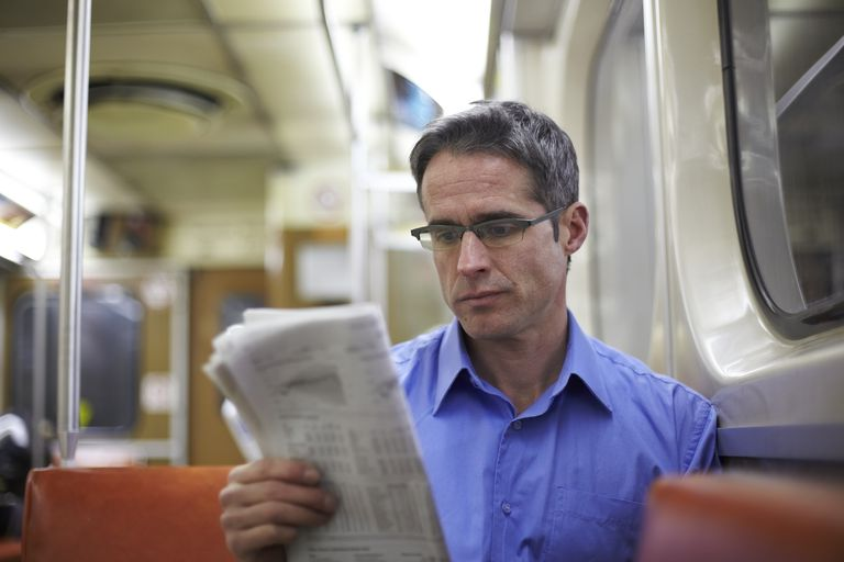 Man Reading Newspaper On Subway