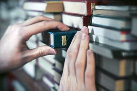 Woman grabbing book from a stack