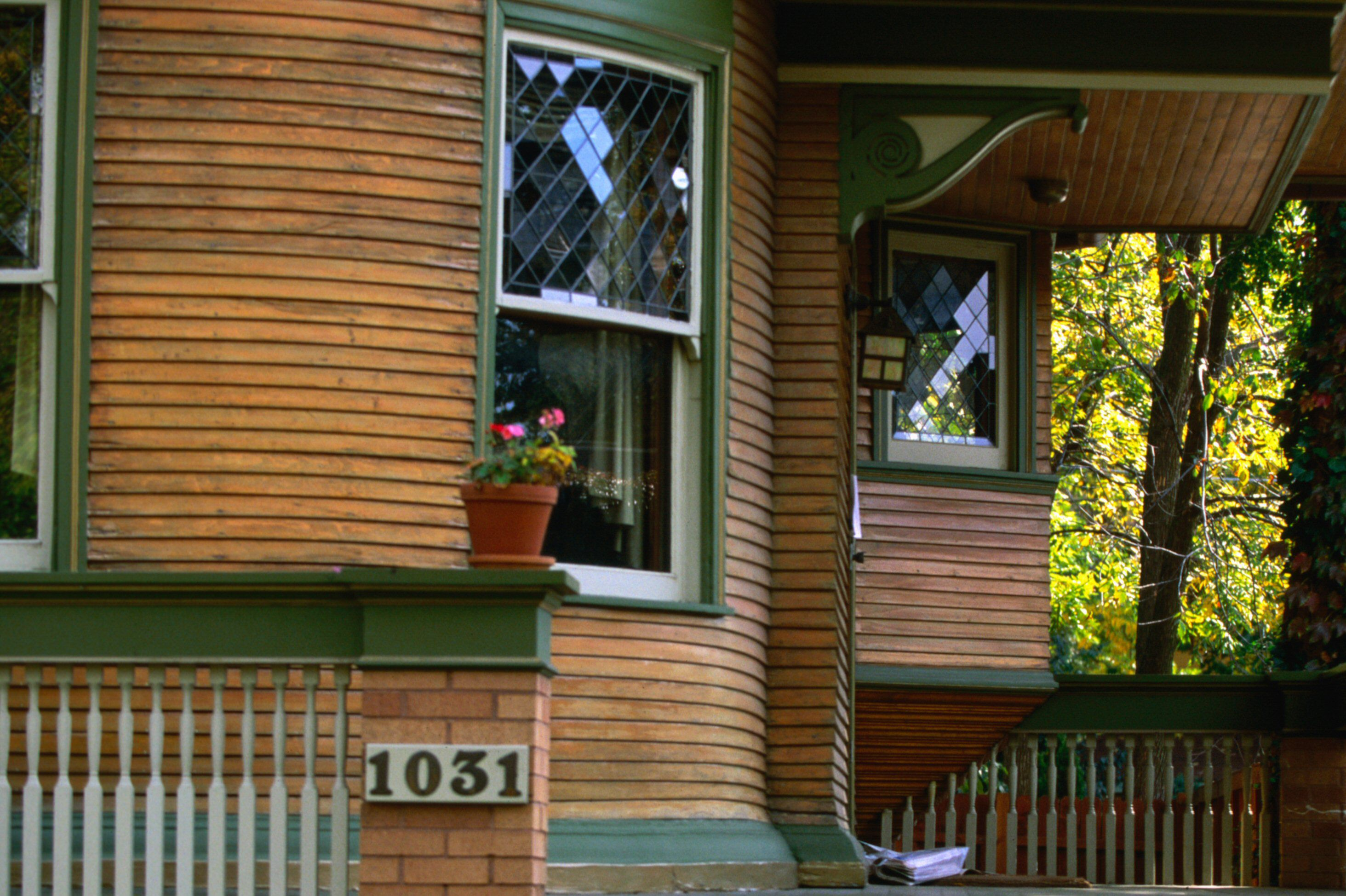Detail of rounded house porch, natural wood siding with green trim, double hung leaded windows, decorative corbels