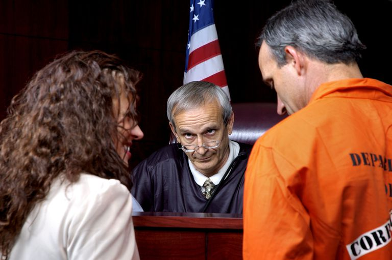 Prison inmate and woman standing before a smirking judge.