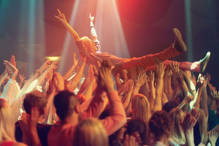 A guy crowd surfing at a concert