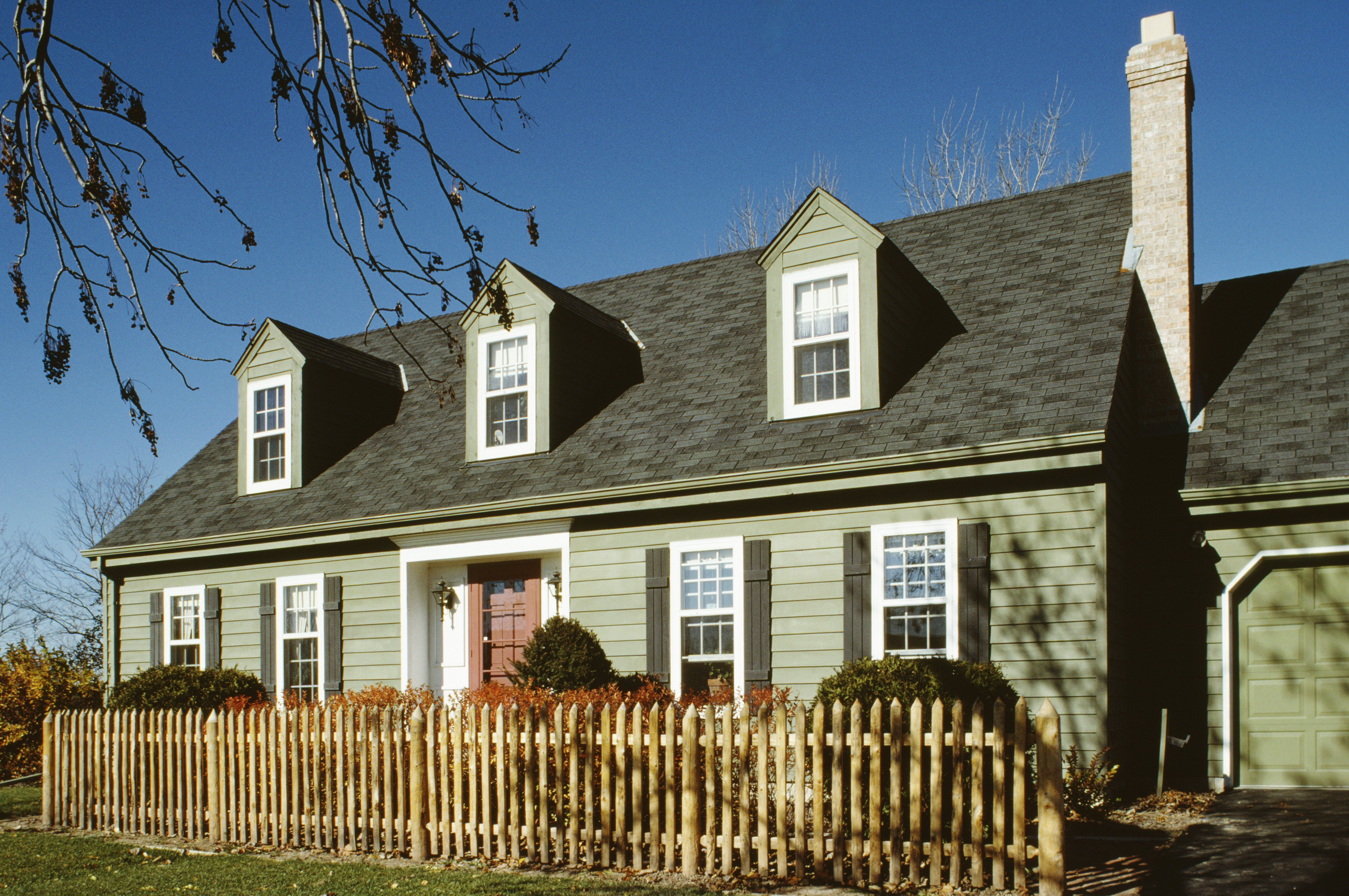 Green Cape Cod style with 3 dormers, 5 bay facade, with entryway recessed beneath a slight roof overhang