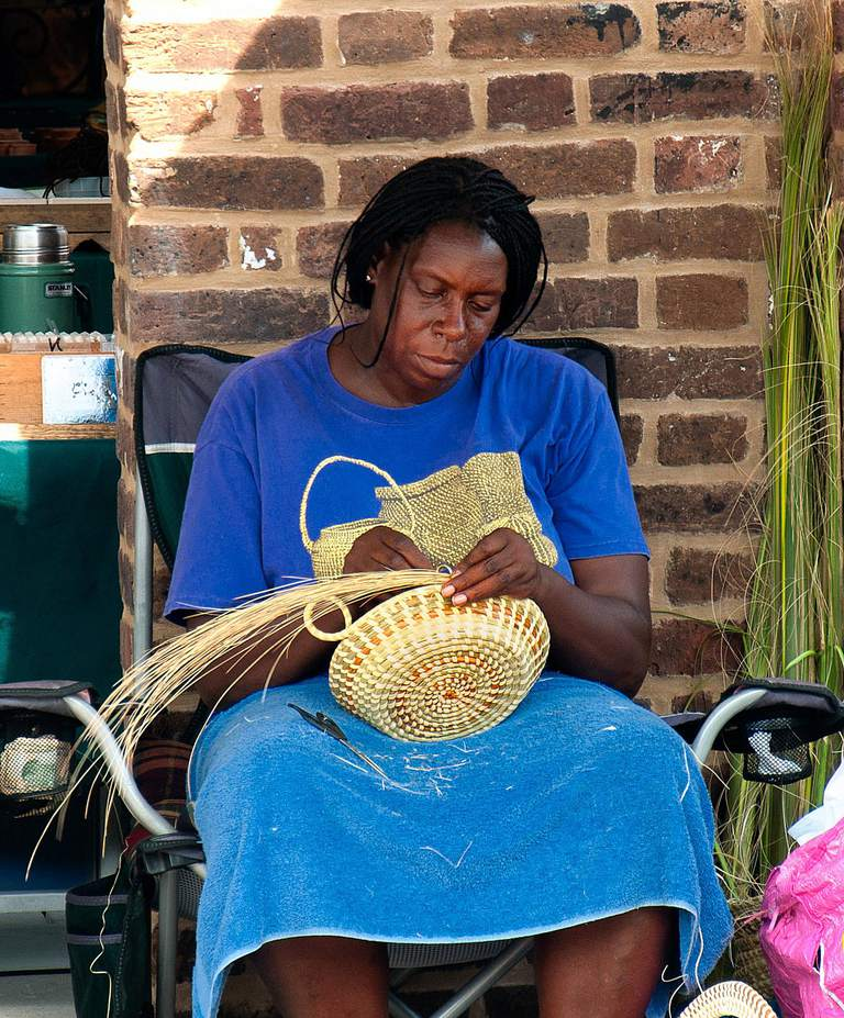 A gullah woman makes a sweetgrass basket in Charleston's City Market