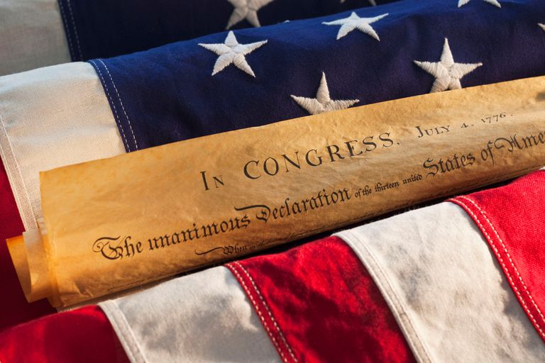 A copy of the declaration of independence rolled up laying in an american flag