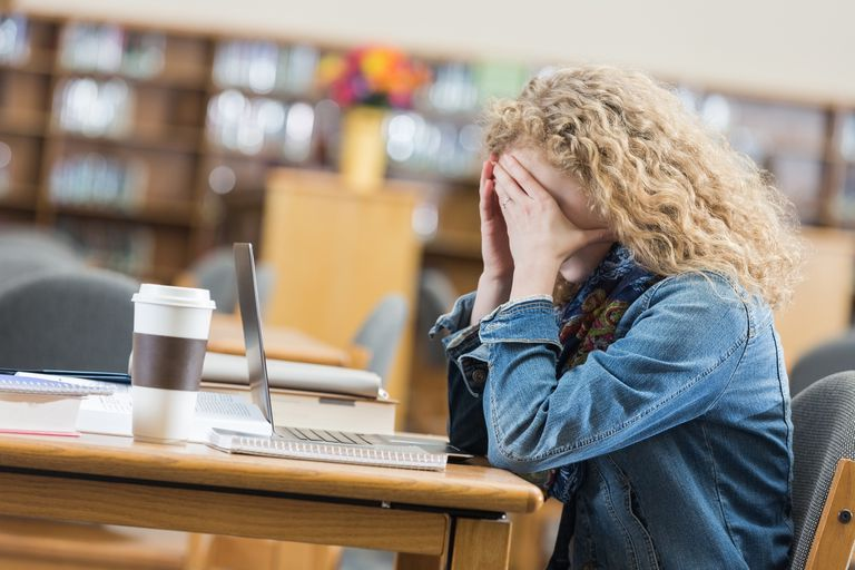 Student frustrated while looking at laptop in school library