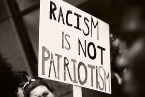 Black and white photo of an anti-racism sign.