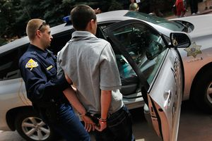 A man being taken into custody by a police officer