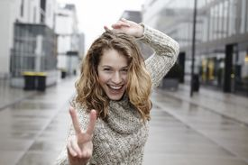 Portrait of happy young woman showing peace sign