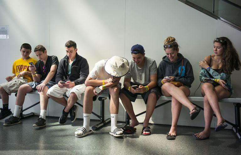 teens sitting on bench using smartphones