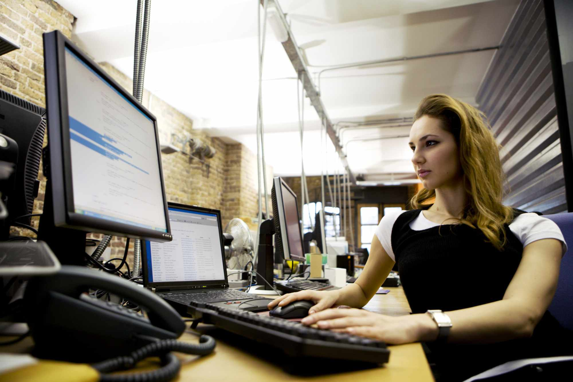 A woman sitting at a desk using a laptop with external keyboard and monitor.