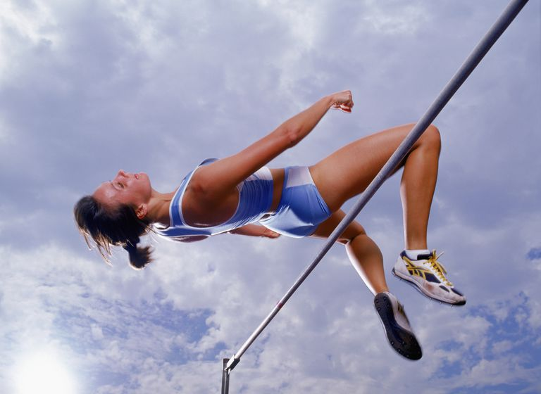 Female high jumper clearing bar