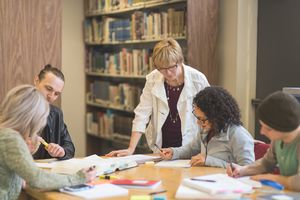 Teacher in library instructing four students