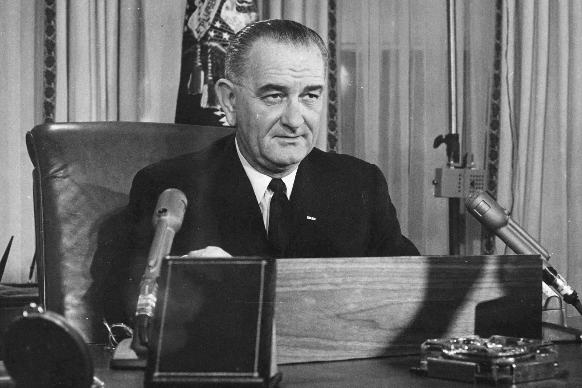 Black and white photo of LBJ speaking into multiple microphones.