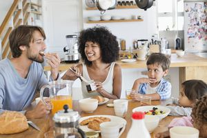 An interracial couple eat breakfast with their children