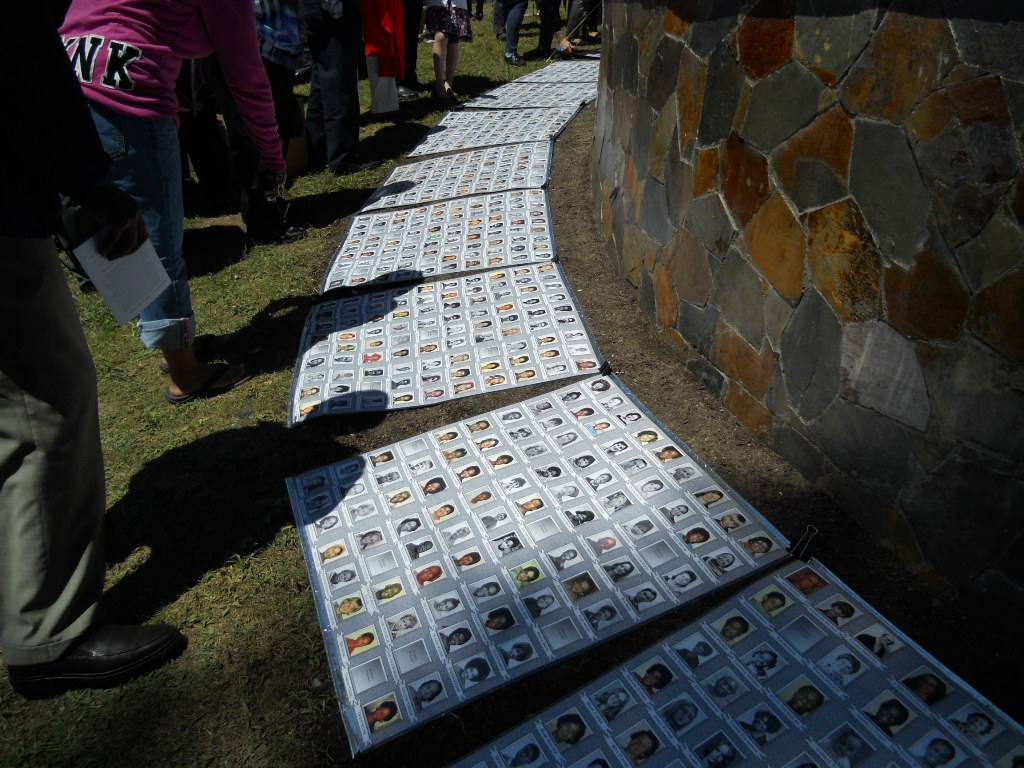Memorial portraits of the Jonestown massacre victims displayed on ground.