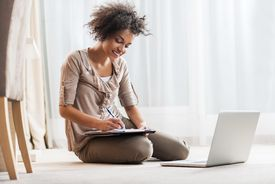 Woman writing on paper in front of laptop
