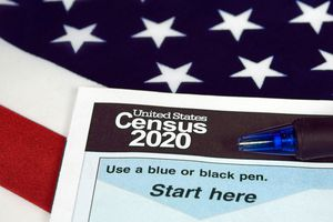A pen and a 2020 United States Census form, with an American flag as the background.