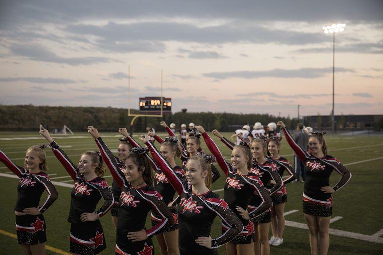Teenage girl high school cheerleaders cheering at sideline of game on football field