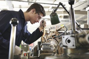 A student working on a metal lathe.