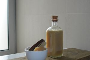 Homemade shampoo in a glass bottle beside a bowl of homemade soap