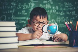 Boy Studying at Table Against Blackboard