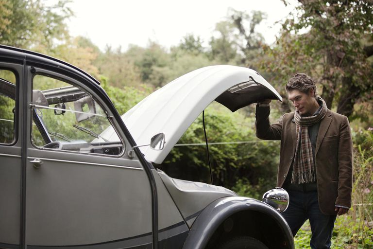 Man Looking Under Hood of Classic Car