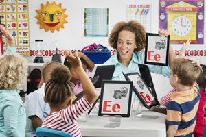 Teacher and students learning alphabet with digital tablets