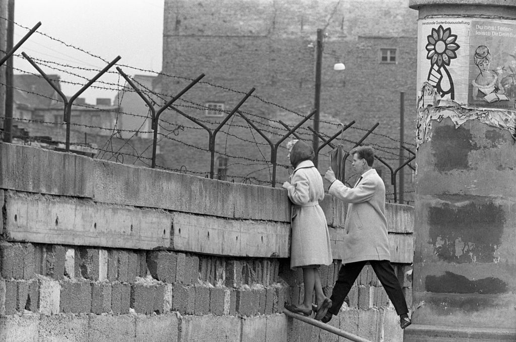 A young woman, accompanied by her boyfriend, stands precariously near the top of the Berlin Wall to talk to her mother on the East Berlin side.