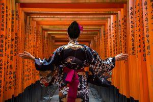 A woman at the entrance to the historic Fushimi Inari-taisha shrine in Kyoto, Japan
